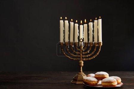 Photo pour Delicious doughnuts near burning candles in menorah on Hanukkah isolated on black - image libre de droit
