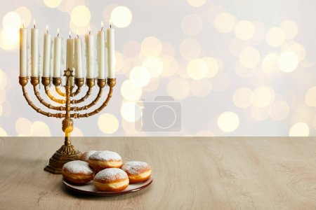 Photo for Delicious doughnuts near candles in menorah on white background with bokeh lights on Hanukkah - Royalty Free Image