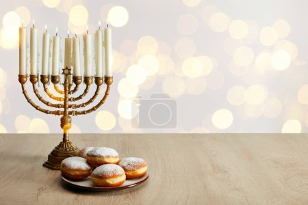 Photo pour Delicious doughnuts near candles in menorah on white background with bokeh lights on Hanukkah - image libre de droit