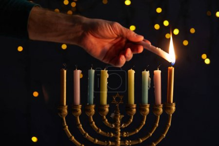 Photo pour Partial view of man lighting up candles in menorah on black background with bokeh lights on Hanukkah - image libre de droit