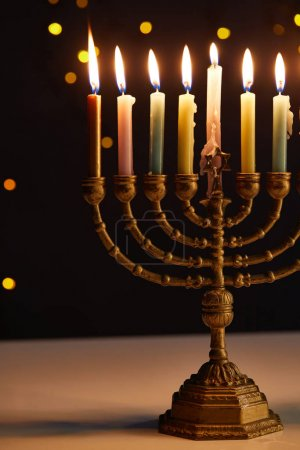 Photo pour Burning candles in menorah on black background with bokeh lights on Hanukkah - image libre de droit