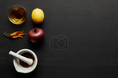 Photo for Top view of olive oil, chill peppers with lemon and onion on black wooden background - Royalty Free Image