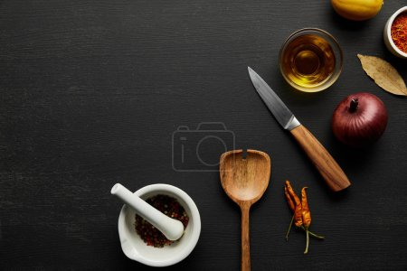 Photo for Top view of wooden spatula, knife with spices and olive oil on black wooden background - Royalty Free Image