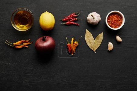 Photo for Top view of spices, olive oil with onion and lemon on black wooden background - Royalty Free Image