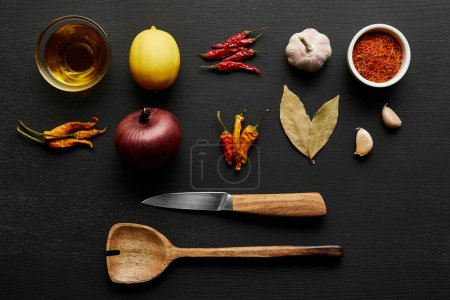 Photo for Top view of spices, olive oil with lemon and onion on black wooden background - Royalty Free Image