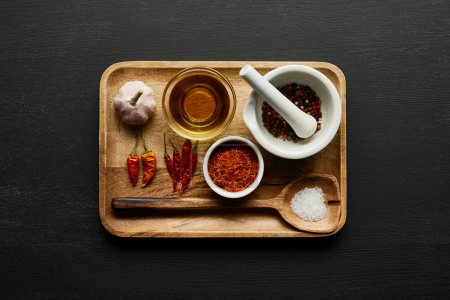 Photo pour Top view of spices, garlic and olive oil on wooden plate on black wooden background - image libre de droit