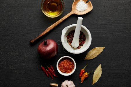 Photo for Top view of spices, olive oil with salt and bay leaves on black wooden background - Royalty Free Image