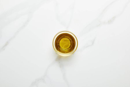 Photo for Top view of olive oil in glass bowl on marble background - Royalty Free Image