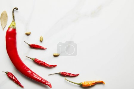 Foto de Top view of chili peppers with cardamom and bay leaf on marble background - Imagen libre de derechos