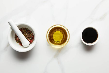 Photo pour Top view of olive oil, soy sauce and peppercorns in bowls on marble background - image libre de droit