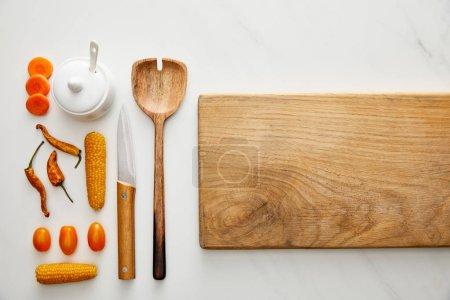 Photo pour Vue en haut de la planche à découper avec ustensiles de cuisine et légumes sur fond de marbre - image libre de droit