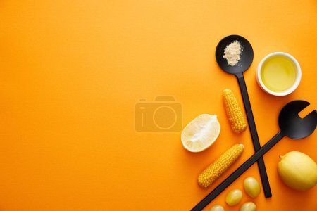 Photo for Top view of kitchenware with olive oil, vegetables and lemons on orange background - Royalty Free Image