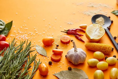 Photo for Fresh rosemary with vegetables and spices on orange background - Royalty Free Image