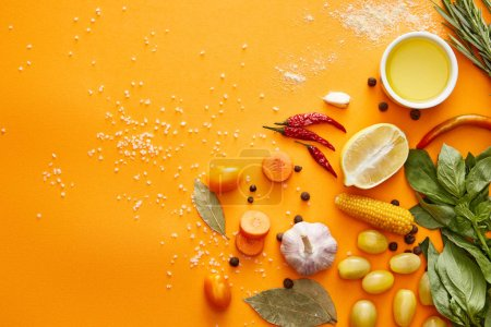 Photo for Top view of fresh vegetables with herbs and spices on orange background - Royalty Free Image