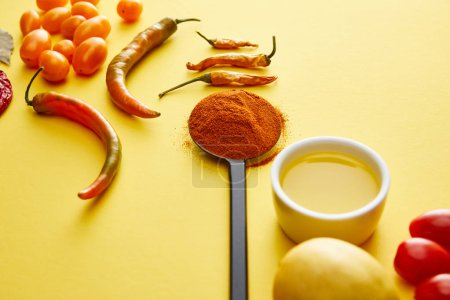 Photo pour Chili peppers with spice and olive oil on yellow background - image libre de droit