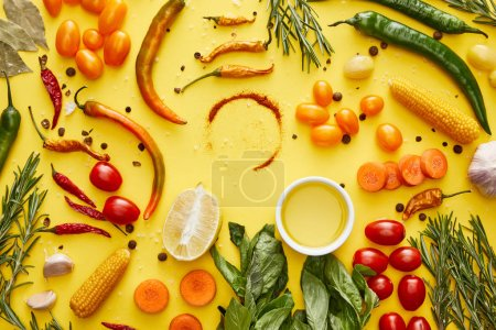 Foto de Top view of organic vegetables and fresh herbs with spices on yellow background - Imagen libre de derechos