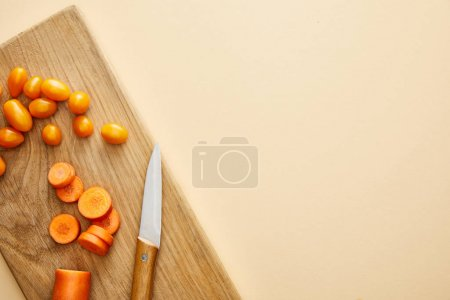 Photo for Top view of carrot and cherry tomatoes with knife on cutting board on beige background - Royalty Free Image
