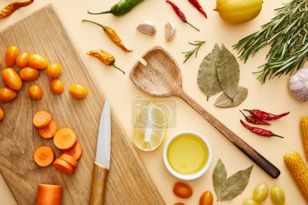 Photo for Top view of fresh vegetables on cutting board and spices on beige background - Royalty Free Image