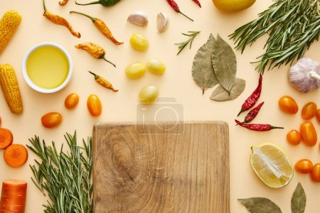 Photo for Top view of cutting board with fresh vegetables and rosemary on beige background - Royalty Free Image