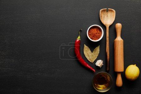 Photo pour Vue en haut du rouleau en bois et de la cuillère avec épices et huile d'olive sur fond noir en bois - image libre de droit