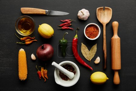 Photo for Top view of kitchenware with organic vegetables and spices on black wooden background - Royalty Free Image