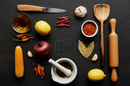 Photo for Top view of wooden kitchenware with ripe vegetables and spices on black wooden background - Royalty Free Image