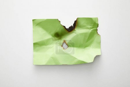 Photo pour Top view of empty crumpled and burnt green paper on white background - image libre de droit