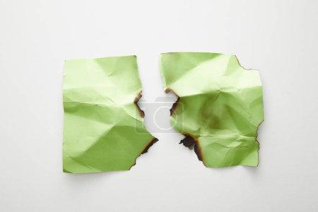 Photo pour Vue du dessus du papier vert froissé, déchiré et brûlé vide sur fond blanc - image libre de droit