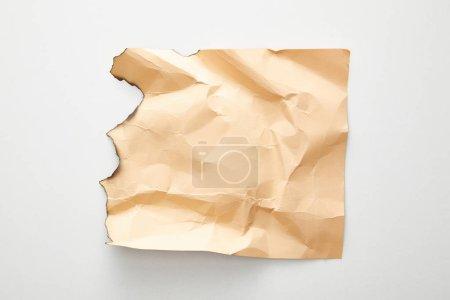 Photo pour Vue du dessus du papier vintage vide froissé et beige brûlé sur fond blanc - image libre de droit