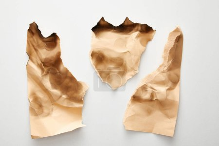 Photo pour Top view of empty crumpled and burnt beige vintage paper pieces on white background - image libre de droit