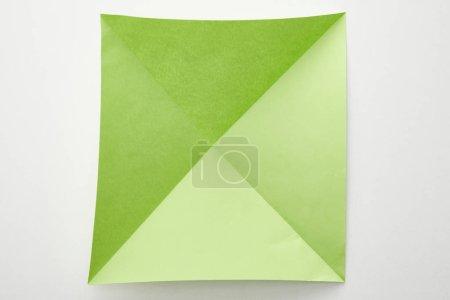 Photo pour Vue de dessus d'un papier origami vert vide sur fond blanc - image libre de droit
