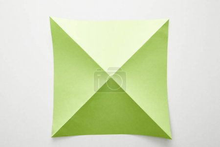 Photo for Top view of empty green origami paper on white background - Royalty Free Image