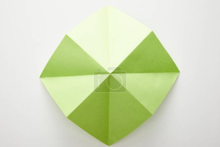 top view of empty green origami paper on white background