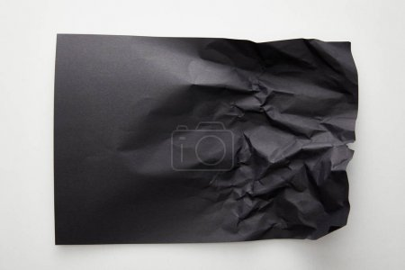 Photo pour Top view of empty crumpled black paper on white background - image libre de droit