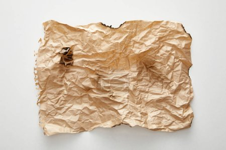 top view of empty beige crumpled and burnt vintage paper on white background