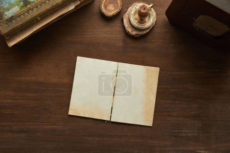 Photo for Top view of vintage notepad, painting, candle and old radio on wooden table - Royalty Free Image