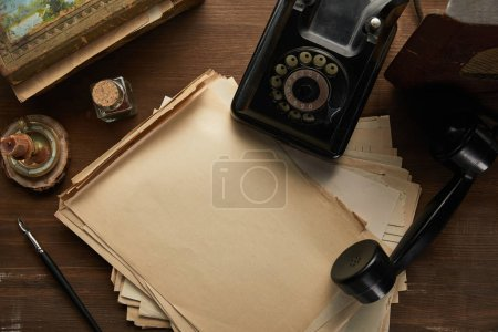 Photo pour Top view of vintage paper, painting, fountain pen, candle and dial phone on wooden table - image libre de droit