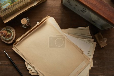 Photo for Top view of vintage paper, painting, fountain pen, stamp and clock on wooden table - Royalty Free Image