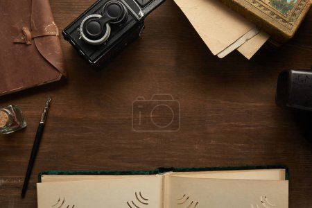 Photo for Top view of vintage camera, photo album, painting, fountain pen on wooden table - Royalty Free Image