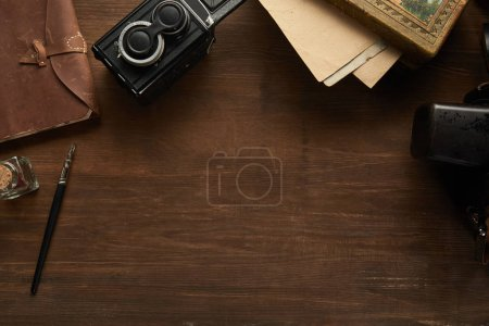 Photo for Top view of vintage camera, paper, painting, fountain pen on wooden table - Royalty Free Image