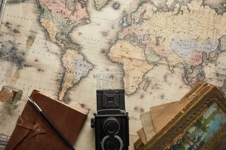 Photo for Top view of vintage camera, notepad with fountain pen and painting on map background - Royalty Free Image