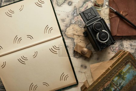 Photo for Top view of vintage camera, notepad with fountain pen, empty photo album and painting on map background - Royalty Free Image