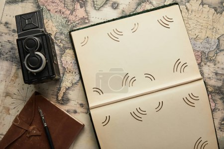 Photo for Top view of vintage camera, notepad with fountain pen, empty photo album on map background - Royalty Free Image