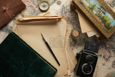 Photo for Top view of vintage camera, compass, fountain pen, photo album, paper and painting on map background - Royalty Free Image