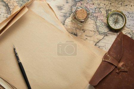 Foto de Vista superior del papel blanco de la época con pluma fuente cerca de la brújula y el bloc de notas de cuero en el fondo del mapa. - Imagen libre de derechos
