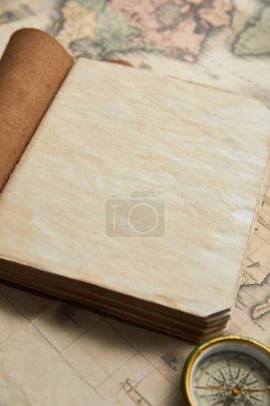 Photo pour Carnet blanc vintage près de la boussole sur fond de carte - image libre de droit