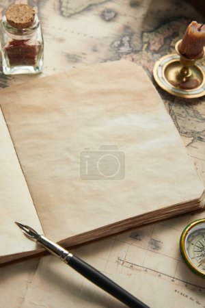 Photo pour Cahier vierge vintage avec plume près de la boussole et bougie sur le fond de la carte - image libre de droit
