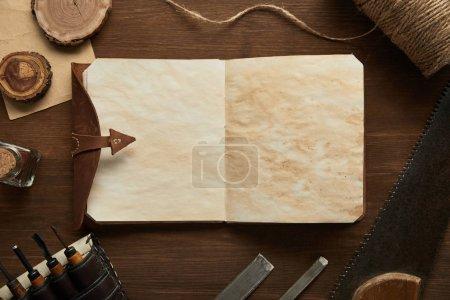widok z góry stary stolarka narzędzia w pobliżu puste vintage notebooka na drewnianym stole