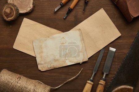 widok z góry na stare narzędzia stolarskie w pobliżu pustych starych papierów na drewnianym stole