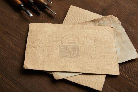 narzędzia stolarskie w pobliżu pustych papierów vintage na drewnianym stole
